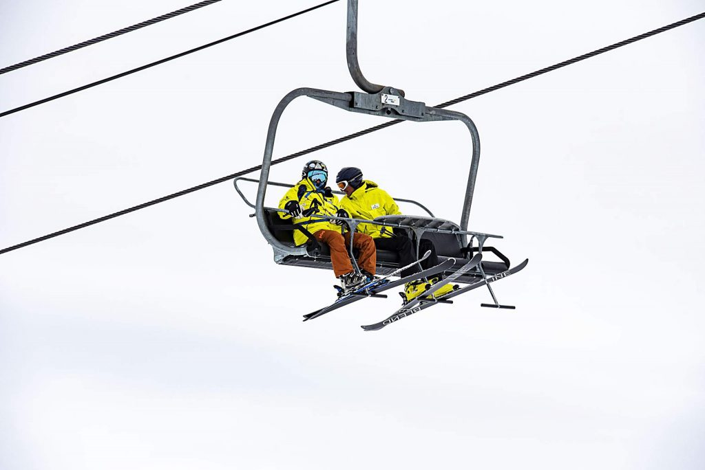 Challenge Aspen skiers watch their friends practice on the NASTAR slalom course as they ride the lift on Snowmass on Thursday, Jan. 30, 2020. (Kelsey Brunner/The Aspen Times)