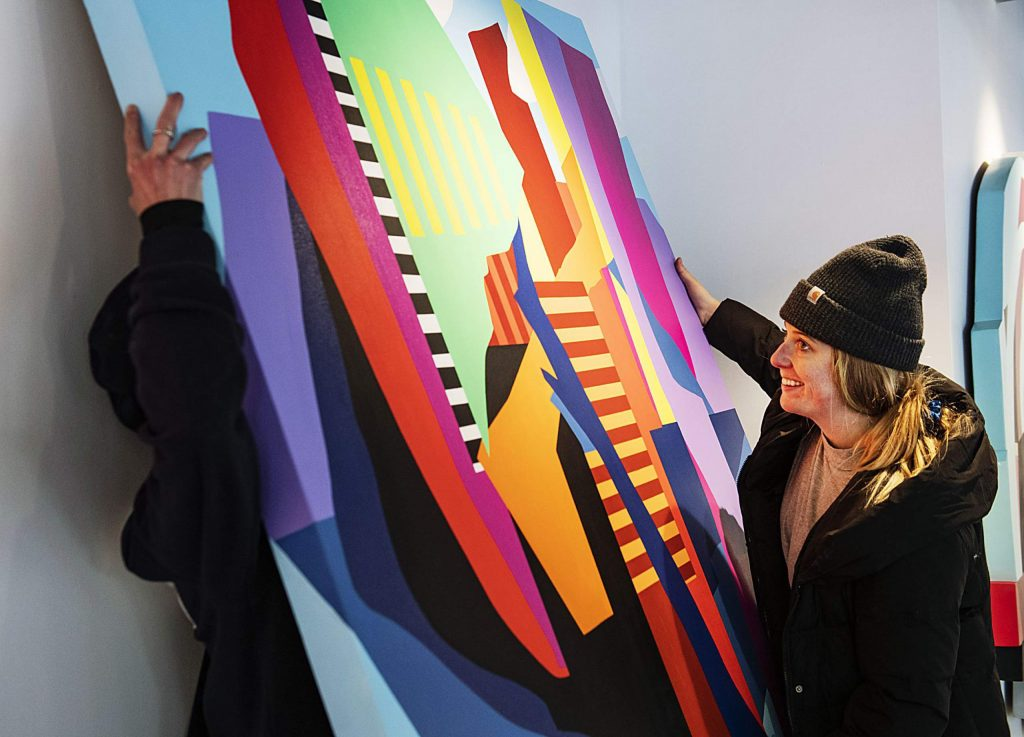Kelly Peters, right, and Teal Roberts Wilson hang work by Chris Erickson in the Straight Line Studio space in Snowmass Base Village for the upcoming show on Thursday, Feb. 13, 2020.