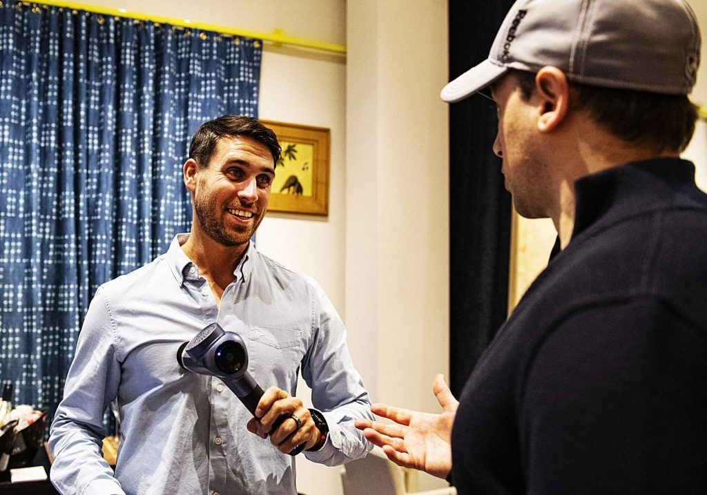 Vibe founder David Mills, left, demonstrates his product while talking to Aspen local personal trainer Jim Marolda during Wellness Wednesday at Here House on Wednesday, Feb. 12, 2020. (Kelsey Brunner/The Aspen Times)