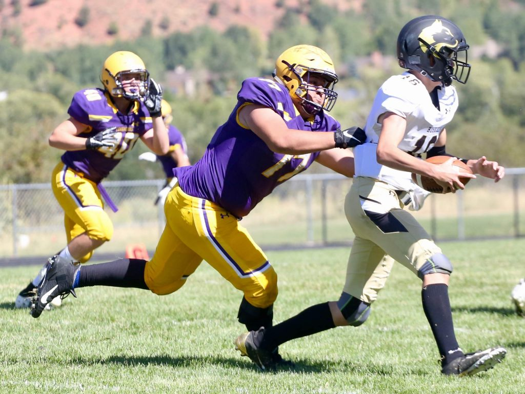Basalt High School football's Ernesto Lopez, left, goes in for a sack against Battle Mountain on Saturday, Sept. 14, 2019, on the BHS field. The Longhorns won, 28-0. (Photo by Austin Colbert/The Aspen Times)