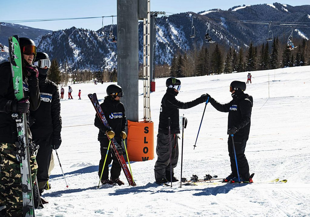 Freeskiers greet each other at the base of the Aspen Snowmass Freeskiing Open course at Buttermilk on Friday, Feb. 14, 2020. (Kelsey Brunner/The Aspen Times)