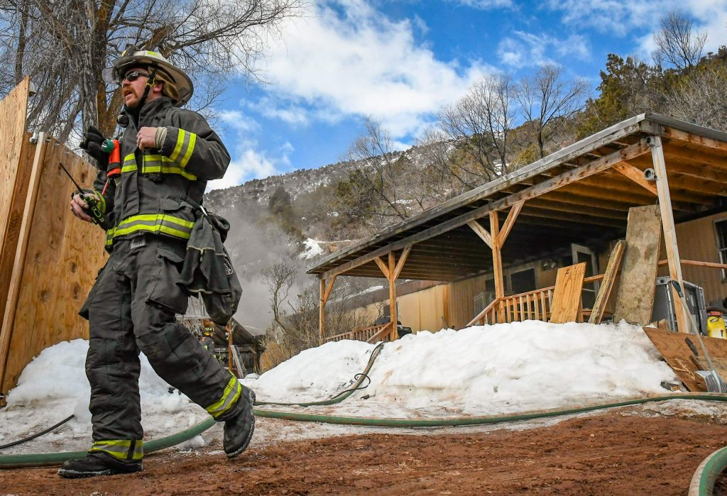 Glenwood Springs Firefighter Harlan Nimmo heads back to the firetruck while battling a mobile home fire in the three-mile area just outside of Glenwood Springs City Limits on Tuesday morning.