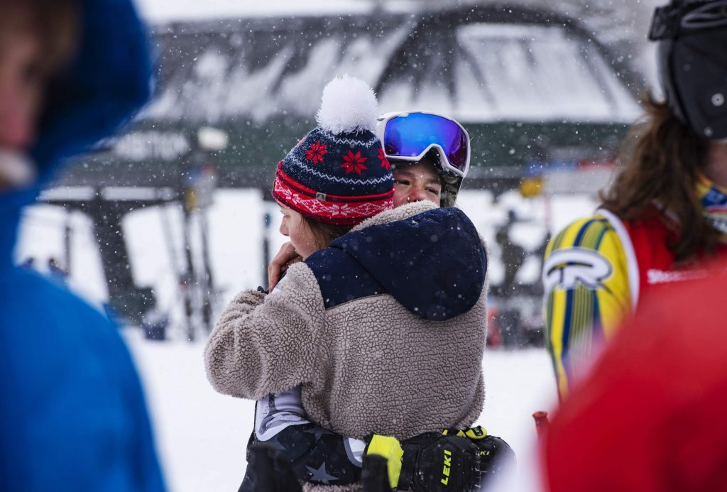 Evelyn Leibinger, left, hugs teammate Jake Morgan after he fell during his first run of the Aspen High School giant slalom at Aspen Highlands on Thursday, Feb. 6, 2020. (Kelsey Brunner/The Aspen Times)