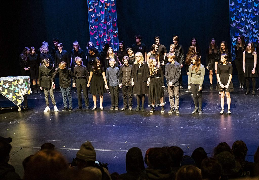 "Aspen Middle School students and faculty stand on the stage holding hands and singing to John Lennon's ""Imagine"" at the conclusion of the Holocaust Remembrance Day Ceremony in the Aspen District Theater on Thursday, Jan. 30, 2020. Decorated butterflies are displayed on stage to represent the children that passed through and died in the concentration camps. (Kelsey Brunner/The Aspen Times)"