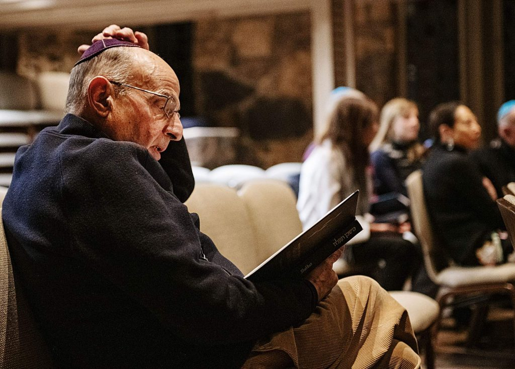 A man reading prayers during a Friday night Shabbat service at the Aspen Chapel.