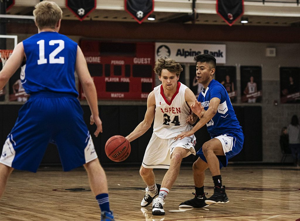 Aspen's Jonathan Woodrow (24) takes the ball up the court while Cedaredge's Fabian Barron (23) plays defense on Saturday, Feb. 22, 2020. (Kelsey Brunner/The Aspen Times)