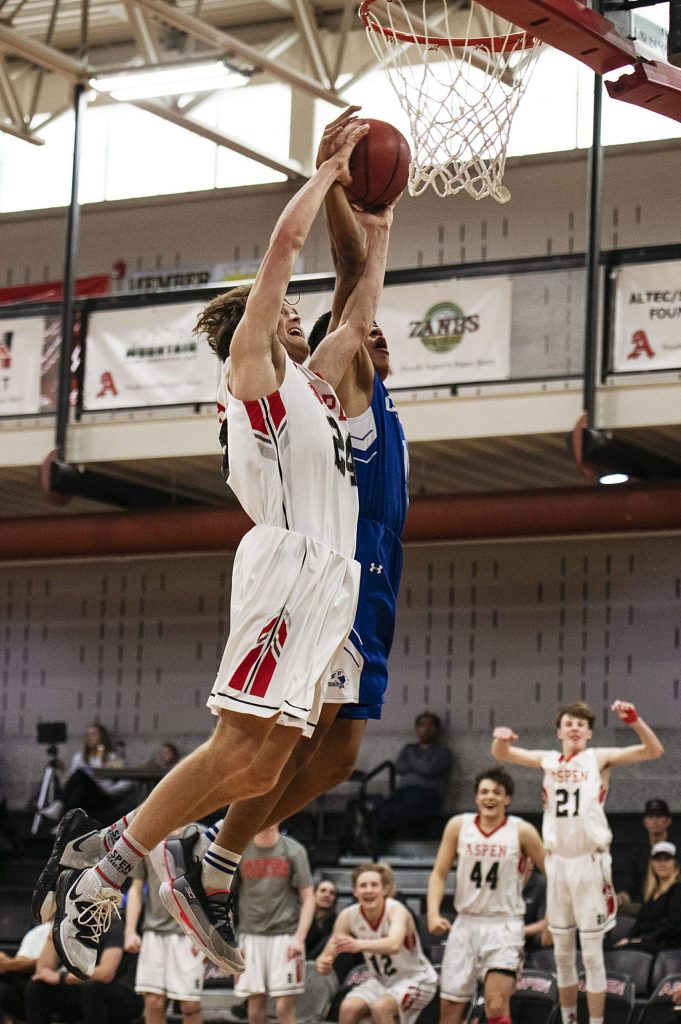 Aspen's Jonathan Woodrow dunks the ball as teammates cheer from the sideline in the game against Cedaredge High School on Saturday, Feb. 22, 2020. (Kelsey Brunner/The Aspen Times)