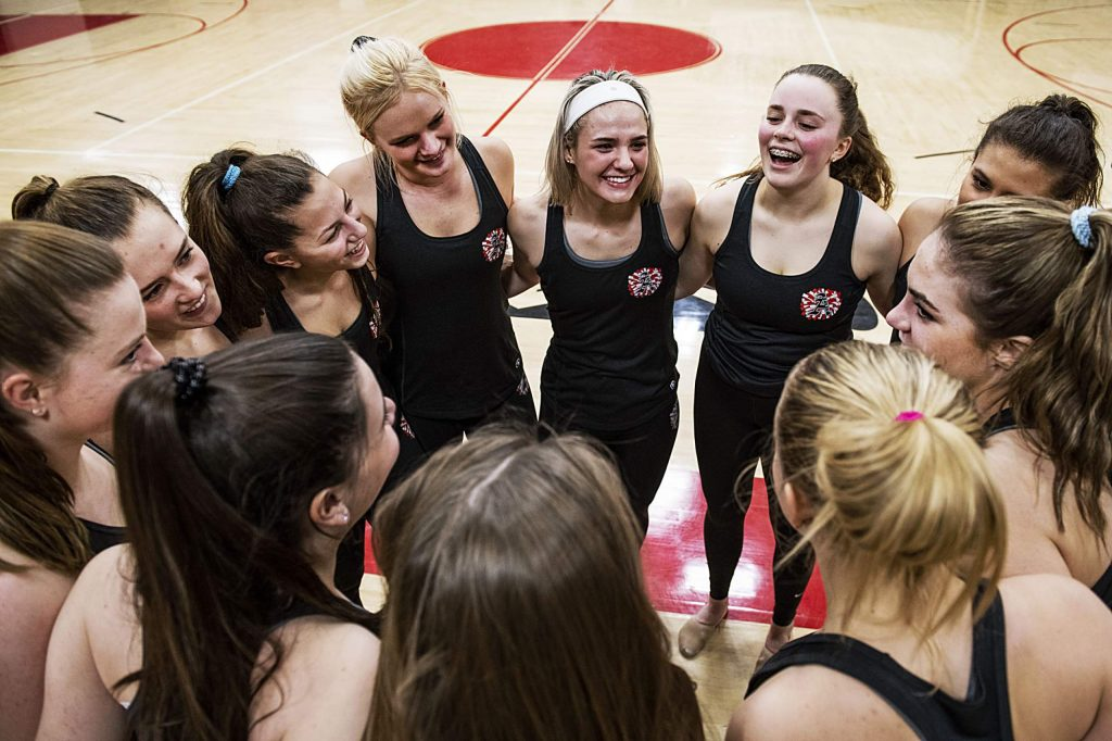 The Aspen High School spirit and dance team huddles before they perform their routines for their parents during the team's sendoff event on Tuesday, March 3, 2020.