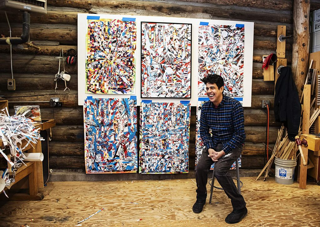 Interdisciplinary artist-in-residence Alejandro Contreras sits in front of his painting laughing about how much he loves his work at Anderson Ranch in Snowmass on Friday, Feb. 21, 2020. (Kelsey Brunner/The Aspen Times)