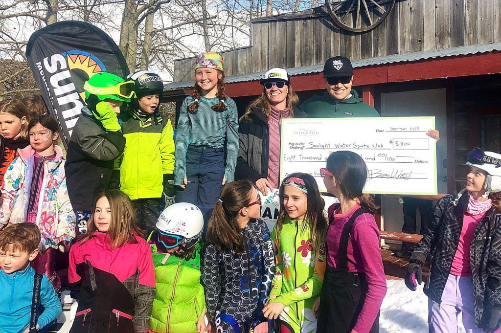 Ben West from Integrated Mountain Properties, upper right, makes the ceremonial check presentation toward a new Sunlight Winter Sports Club clubhouse, with Buddy Werner coach Caroline Rubin and several Buddy Werner athletes present during the championships March 1.