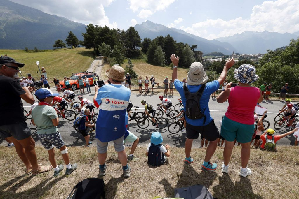 FILE - In this file photo taken on July 26, 2019 spectators along the road applaud the riders during the nineteenth stage of the Tour de France cycling race between Saint Jean De Maurienne and Tignes. Swarms of fans clog the city streets, winding roads and soaring mountain passes of the Tour de France during cycling's three-week showpiece. But unlike almost every other major sporting event it has yet to be called off because of the coronavirus and the start date remains June 27. The new coronavirus causes mild or moderate symptoms for most people, but for some, especially older adults and people with existing health problems, it can cause more severe illness or death. (AP Photo/Thibault Camus, File)
