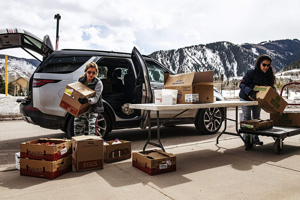 Elizabeth Slossberg, left, and Lisa DiMento unload boxes of donated food from Bonnie's at the Aspen Middle School food drop-off on Wednesday, March 18, 2020.
