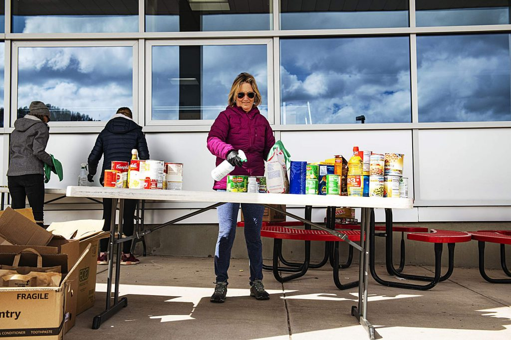 Karen Hawkes, center, sanitizes donated nonperishable items outside of Aspen Middle School during a food drive put on through Aspen Family Connections on Wednesday, March 18, 2020. Boxes will be ready for pickup on Saturday.