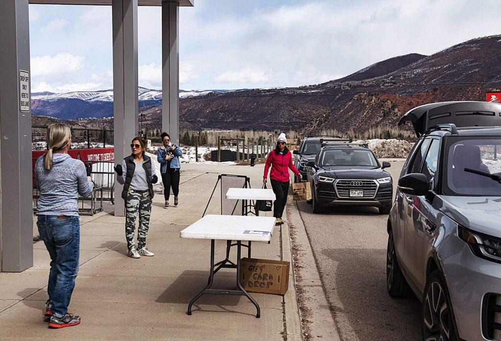 Cars line up at the food drop-off table outside of Aspen Middle School on Wednesday, March 18, 2020.