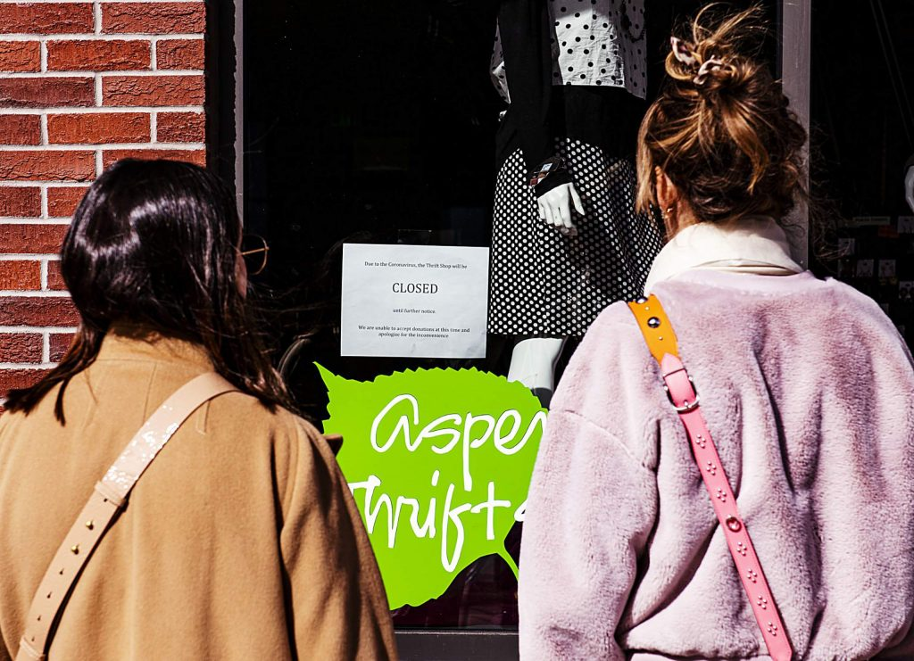 Two women look at the Aspen Thrift Shop's notice of closure due to the coronavirus on Thursday, March 12, 2020. (Kelsey Brunner/The Aspen Times)