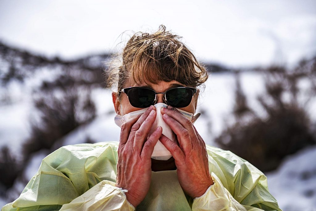 A healthcare provider puts a fit-tested mask over her face before her next patient at the coronavirus testing location at the Aspen Volunteer Fire Department's Aspen Village Location on Thursday, March 12, 2020.
