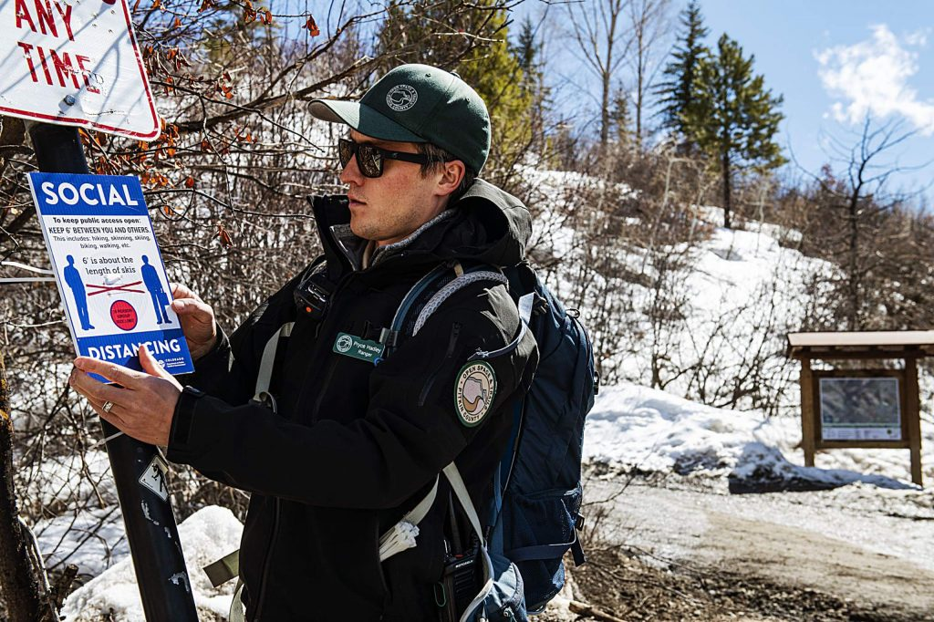 Pitkin County Open Space and Trails ranger Pryce Hadley puts a new social distancing sign at the trailhead of Smuggler Mountain Road on Tuesday, March 24, 2020. The sign urges people to follow the social distancing guidelines to help keep access to public spaces available during the COVID-19 pandemic. (Kelsey Brunner/The Aspen Times)