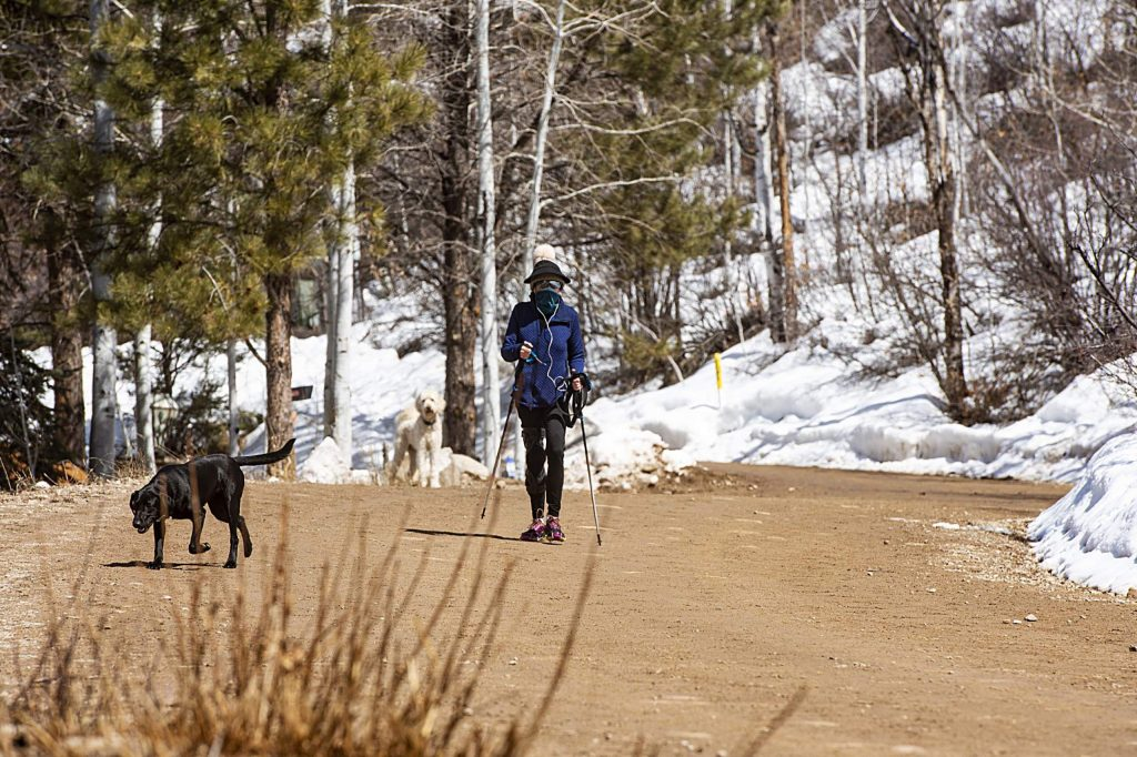 A woman walks her dog with her mouth and nose covered on Smuggler Mountain Road in Aspen on Tuesday, March 24, 2020. (Kelsey Brunner/The Aspen Times)