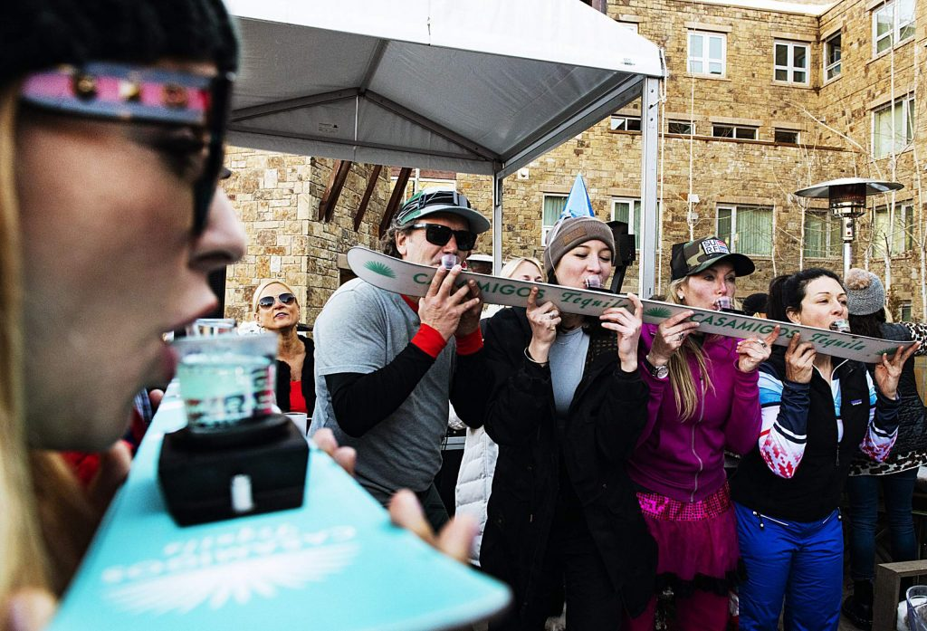 People take shot skis during the Snow Lodge Aprés on Thursday, March 5, 2020.