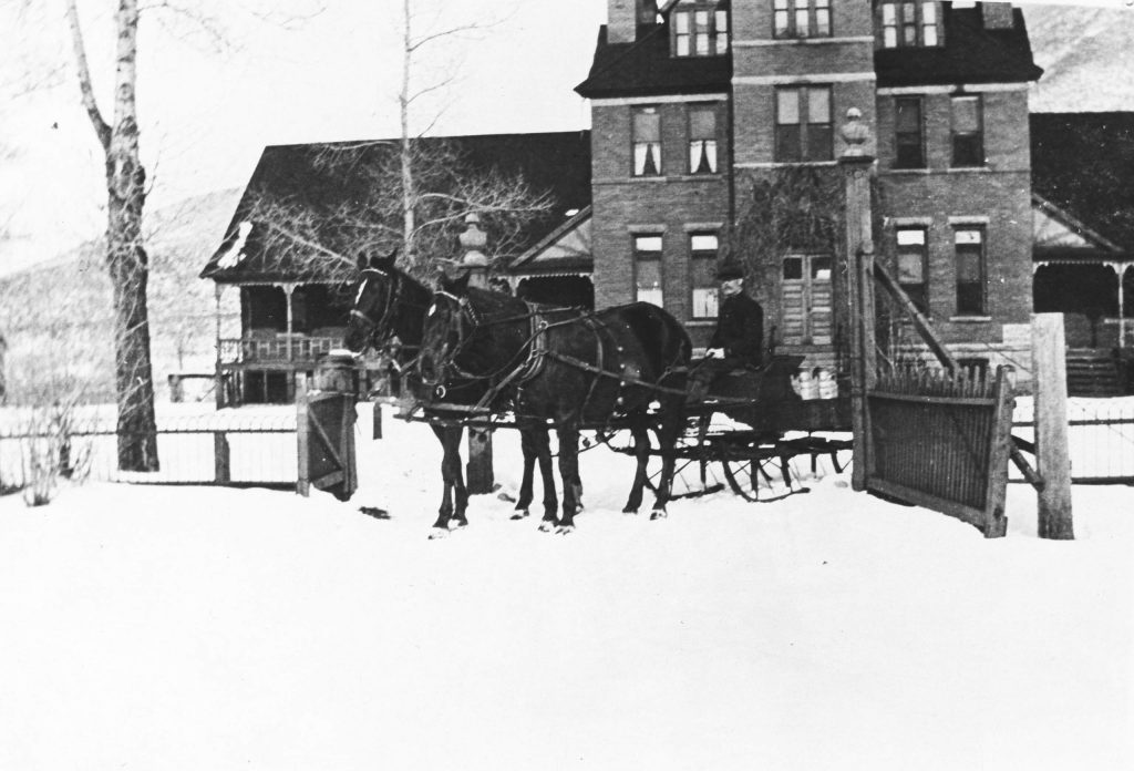 A sleigh pulled by two horses going through the gate of the Citizens Hospital, photographed in the 1910s.