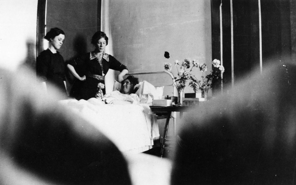A patient lying with visitors at Citizen's Hospital in Aspen, 1913.