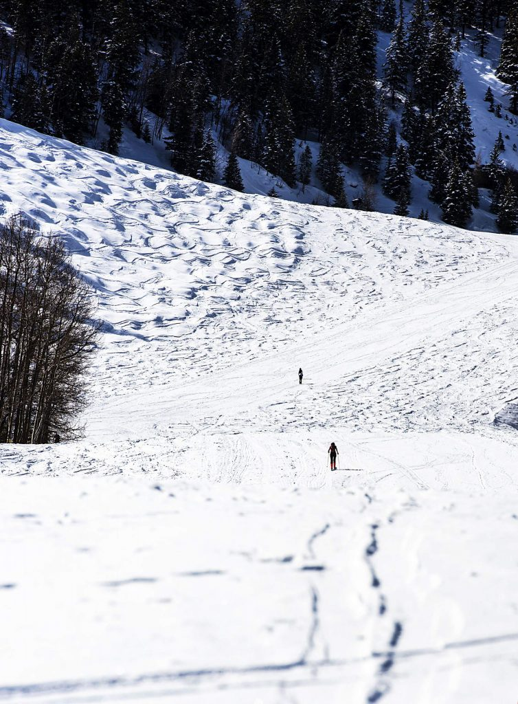 People skin up Aspen Mountain after the announcement that the ski resorts have officially closed for the season on Saturday, March 21, 2020. (Kelsey Brunner/The Aspen Times)