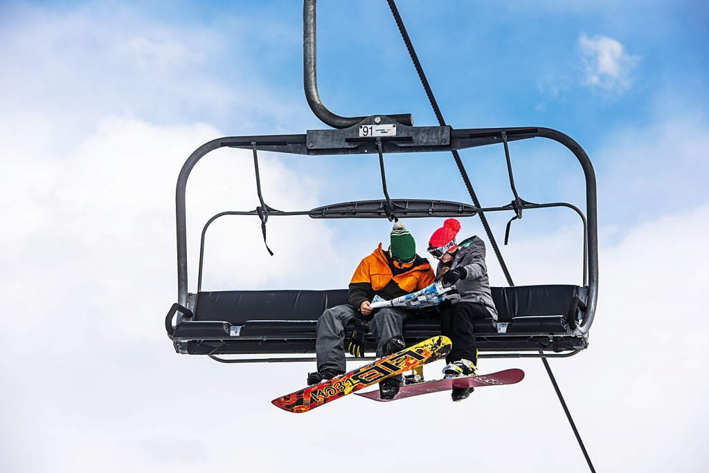 Two snowboarders read a map on the Village Express lift in Snowmass on Saturday, March 14, 2020. (Kelsey Brunner/The Aspen Times)