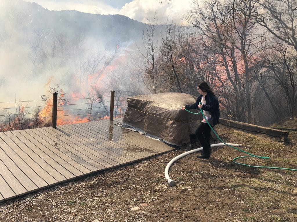 Homeowner Susan Nicholson uses a garden hose Wednesday afternoon to wet down her back deck as well as grass and brush around it as a wild land fire spreads on adjoining BLM land near El Jebel.