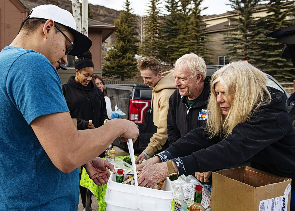 Gwyn Knowlton, right, and George Gordon, center right, along with other people from Gwyn's High Alpine pass out food supplies to Snowmass community members on Tuesday, March 17, 2020. (Kelsey Brunner/The Aspen Times)