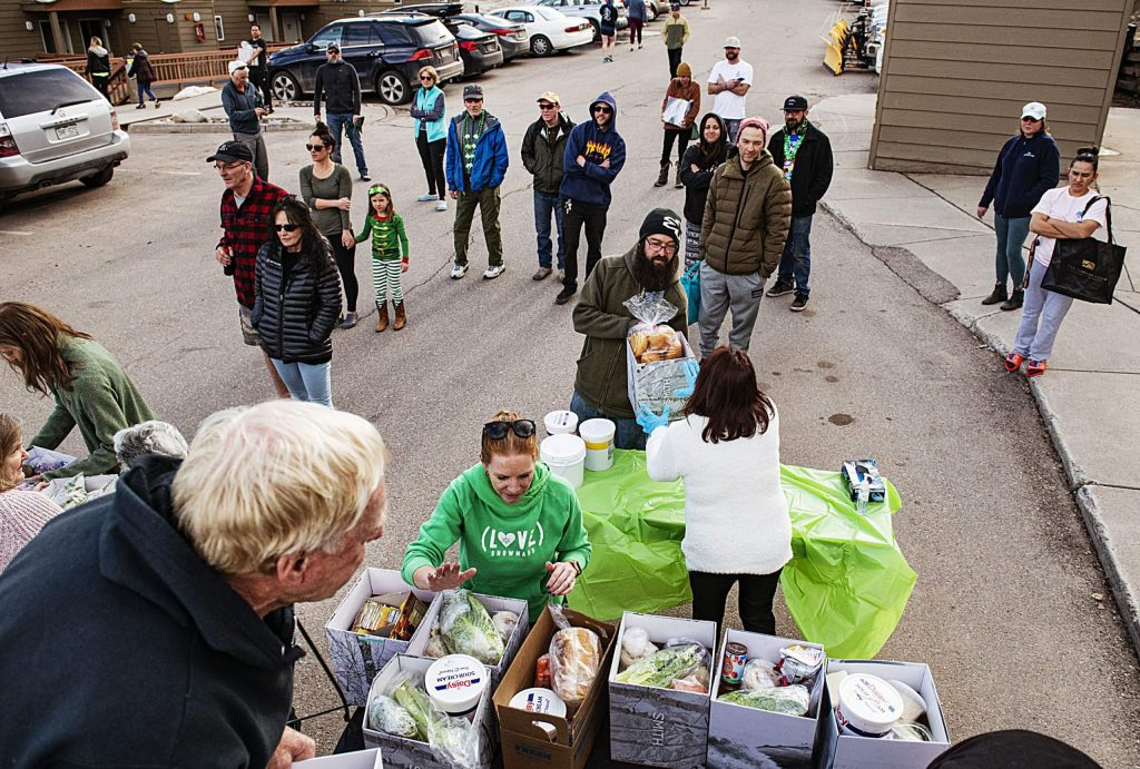 George Gordon, left, Whitney Gordon, center left, and other people from Gwyn's High Alpine hand out the restaurant's food supplies to Snowmass community members in the parking lot of the Housing Office on Tuesday, March 17, 2020. (Kelsey Brunner/The Aspen Times)