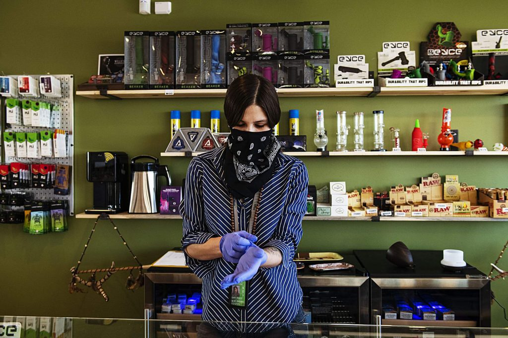High Q store manager Leah Thomas puts on a bandana and gloves for health safety before opening at noon in Snowmass Village Mall on Tuesday, March 31, 2020. (Kelsey Brunner/The Aspen Times)