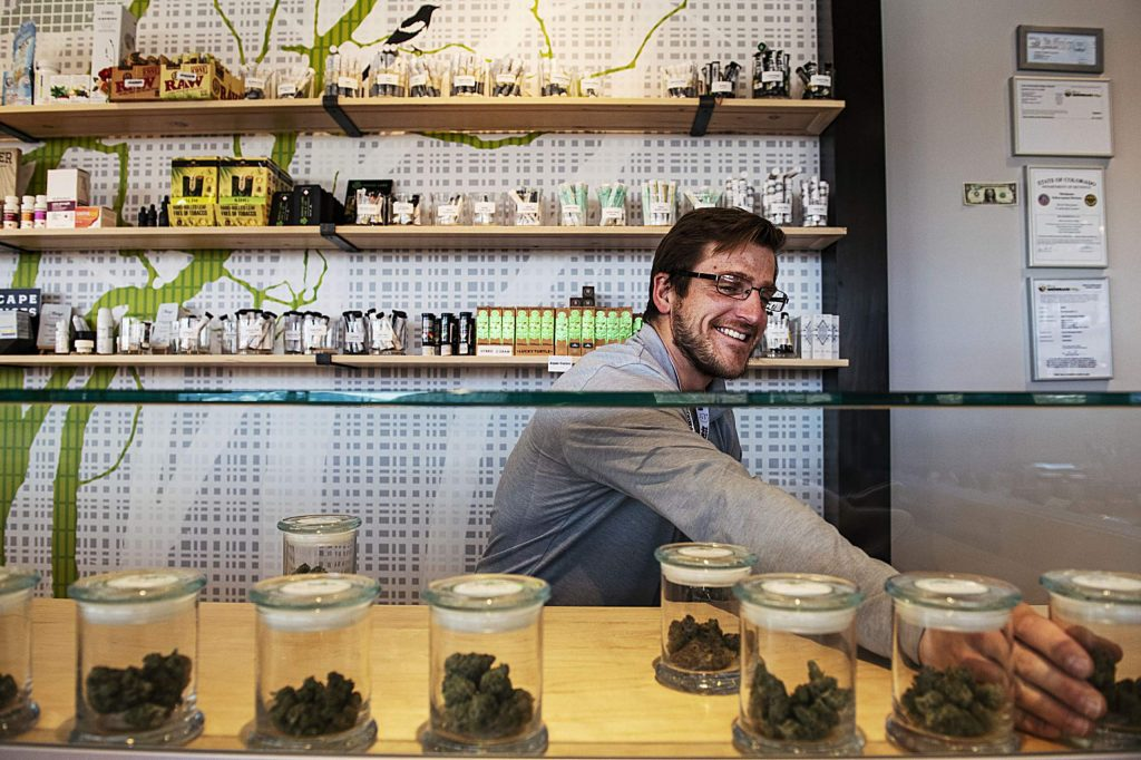 High Q budtender Curtis Jones puts the shop's flower in the display case before opening at noon in Snowmass Village Mall on Tuesday, March 31, 2020. (Kelsey Brunner/The Aspen Times)