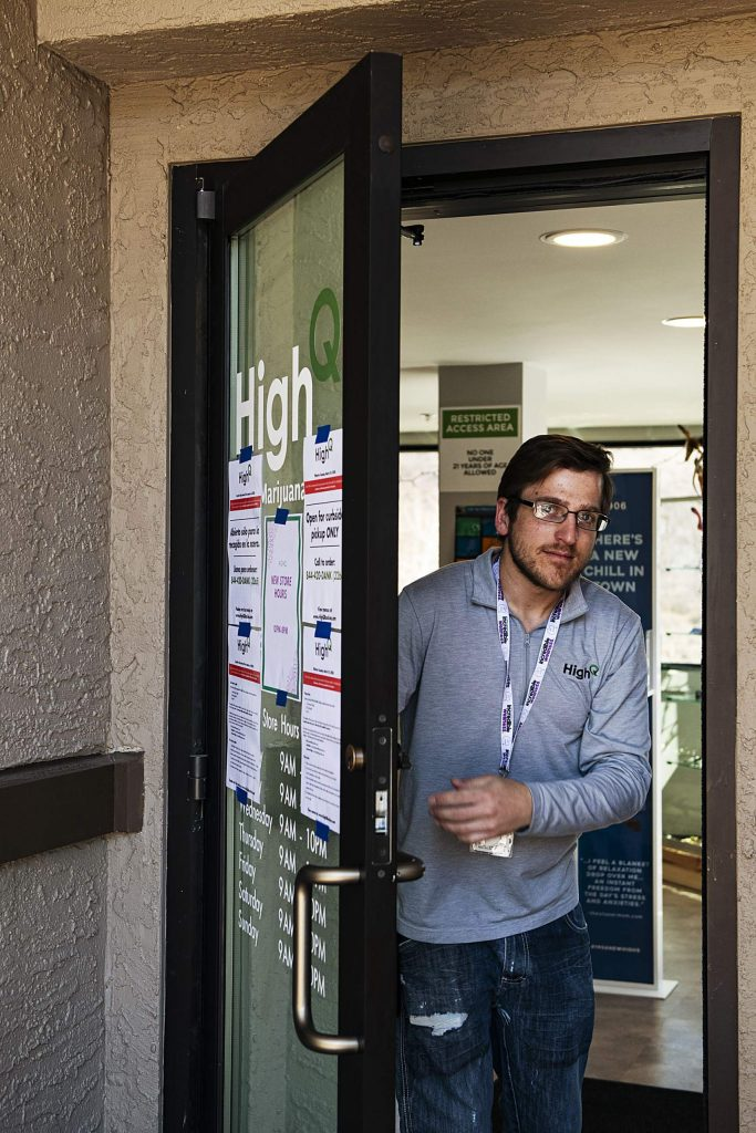 "Curtis Jones opens High Q's door that has signs explaining that the shop is ""curbside pick-up only"" in Snowmass Village Mall on Tuesday, March 31, 2020. (Kelsey Brunner/The Aspen Times)"