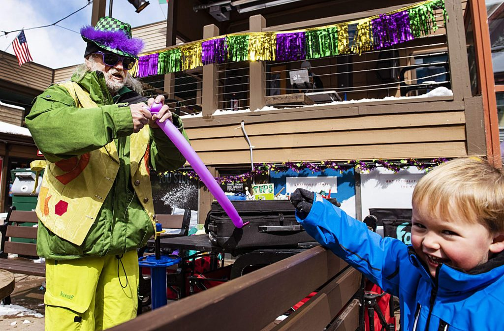 Kristof Kosmowski, left, ties a balloon for Renan Pottle, 3, in the Snowmass Village Mall during the Mardi Gras carnival on Tuesday, Feb. 25, 2020. (Kelsey Brunner/The Aspen Times)
