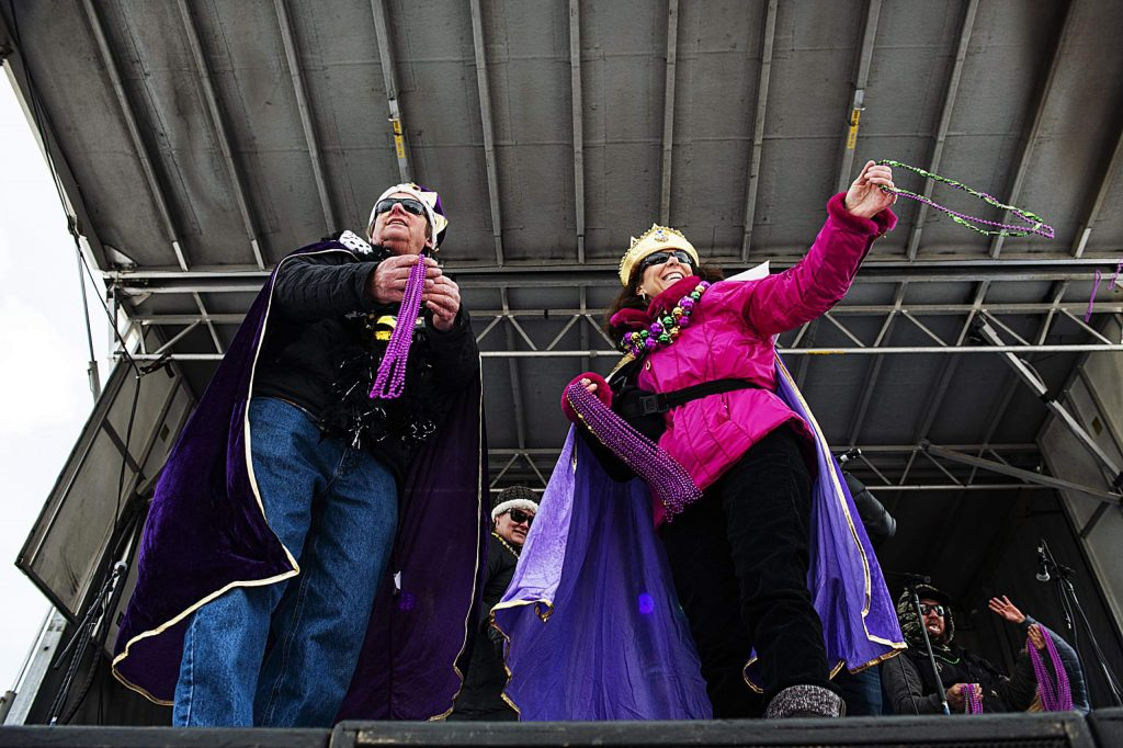 Mardi Gras King and Queen, Duke Taylor, left, and Julie Schoppermele toss beads from the stage in Snowmass Base Village on Tuesday, Feb. 25, 2020. (Kelsey Brunner/The Aspen Times)