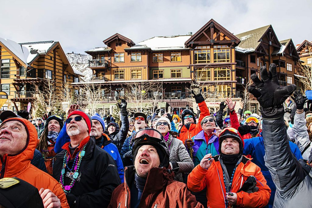 People catch beads in Snowmass Base Village during the Mardi Gras event on Tuesday, Feb. 25, 2020. (Kelsey Brunner/The Aspen Times)