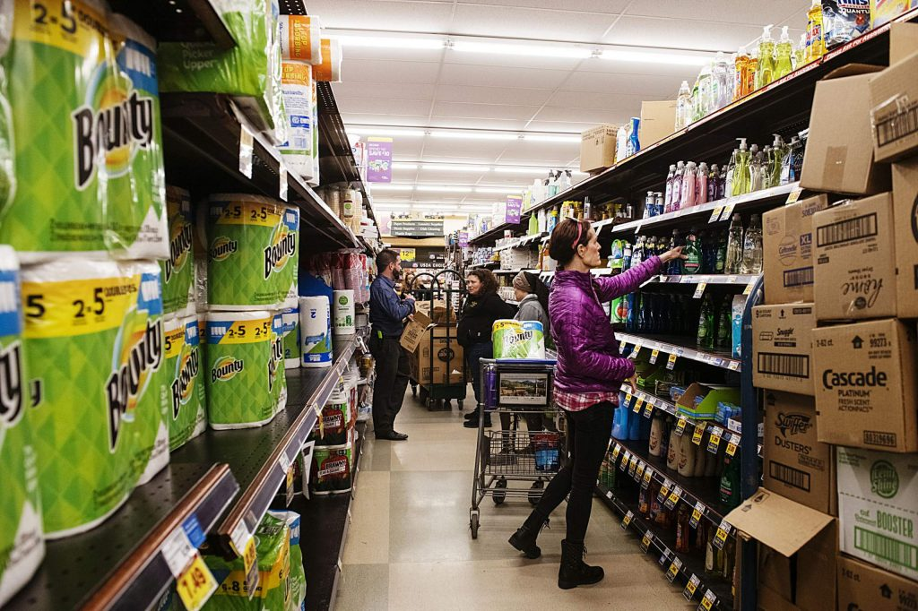 Customers shop for cleaning products as City Market employees restock shelves on Friday, March 13, 2020.