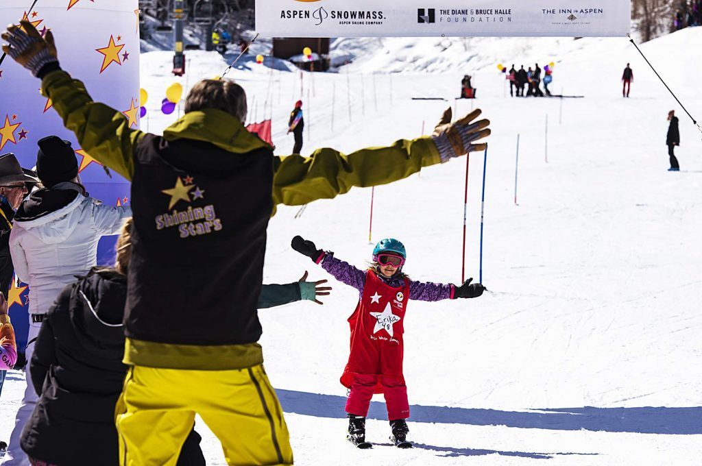 Shining Stars' Erika Grigoryan, 9, celebrates with a cheering audience as she crosses the race finish line during the Aspen Winter Games at Buttermilk on Thursday, March 5, 2020.