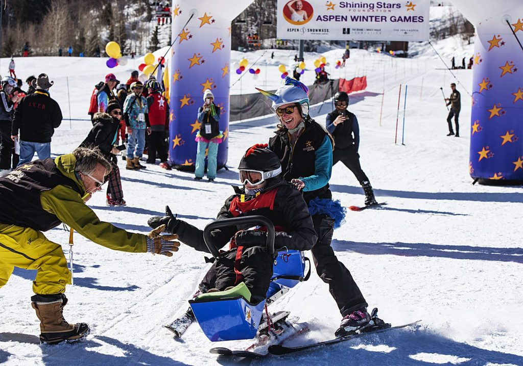 Shining Stars volunteer David Bach claps hands with children as they finish their runs during the Aspen Winter Games at Buttermilk on Thursday, March 5, 2020.