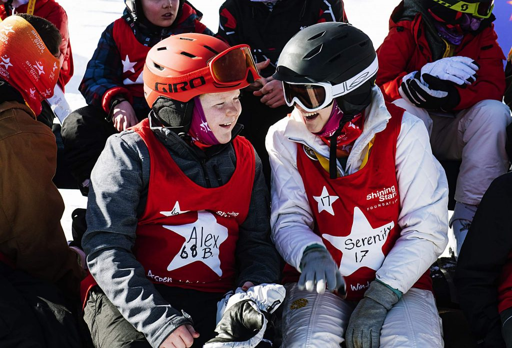 Shining Stars' Alex Brown, 15, left, and Serenity Gibney, 16, talk before taking a group picture during the Aspen Winter Games at Buttermilk on Thursday, March 5, 2020.