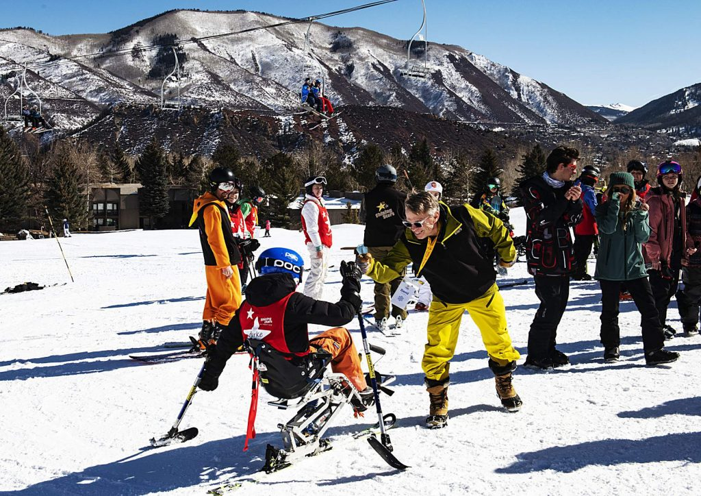 Shining Stars' Burke Ryder, 15, claps hands with volunteer David Bach after finishing his run during the Aspen Winter Games at Buttermilk on Thursday, March 5, 2020. Ryder was on the Breckenridge Ski Team until he received his diagnosis in 8th grade. He said he's considered getting into adaptive ski racing.