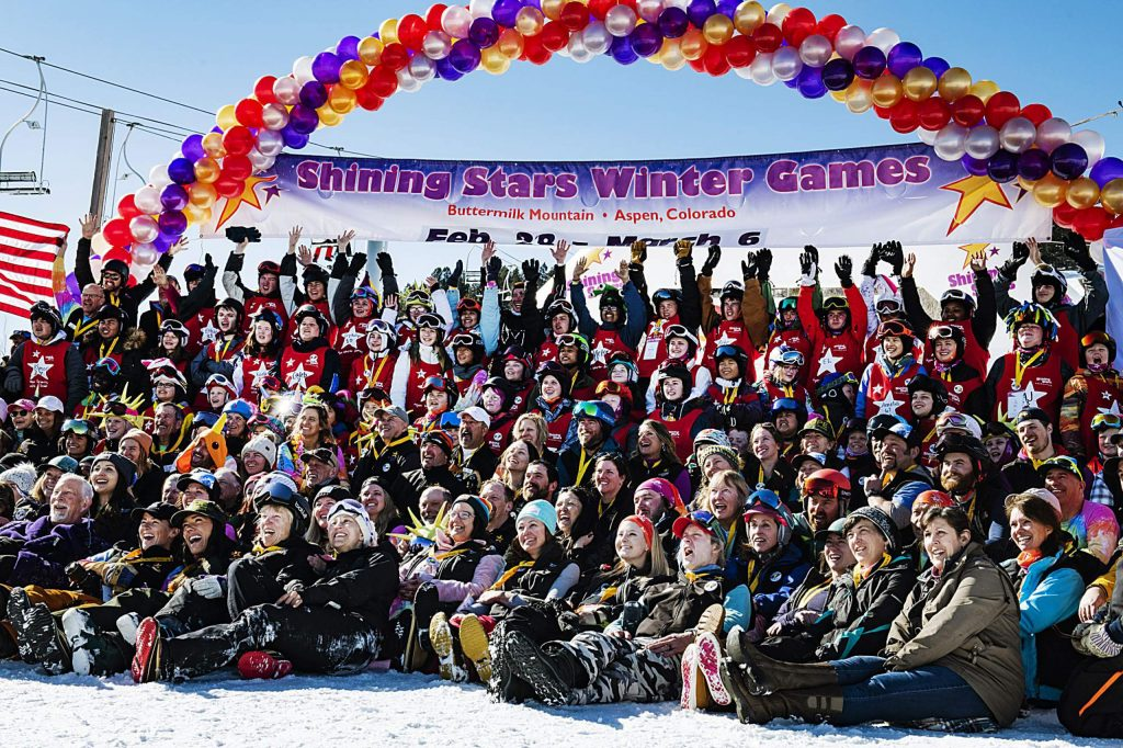 The Shining Stars crew pose for a large group photo under the race banner before the start of the Aspen Winter Games at Buttermilk on Thursday, March 5, 2020.