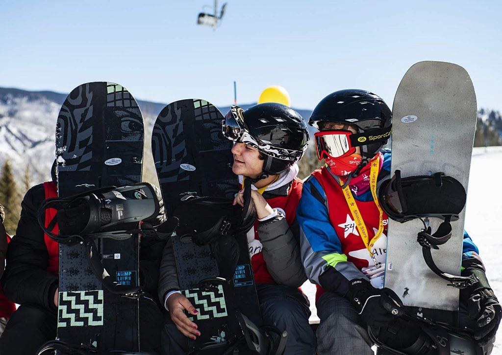 Shining Stars talk from behind their snowboards at the top of the race course during the Aspen Winter Games at Buttermilk on Thursday, March 5, 2020.