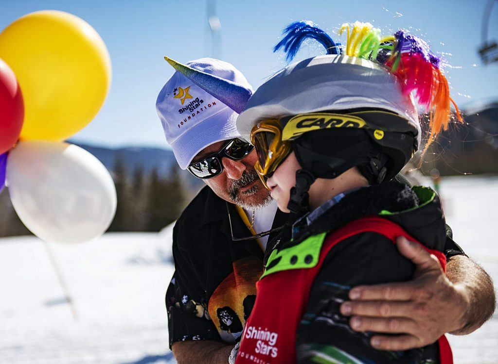 A Shining Stars volunteer gives advice to a child before their race during the Aspen Winter Games at Buttermilk on Thursday, March 5, 2020.