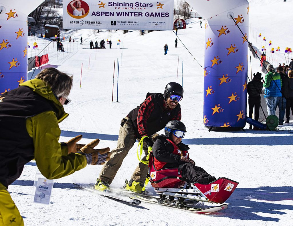Shining Stars' Tony Enriquez, 9, crosses the finish line with his ski instructor, Billy Meyer, as David Bach, left, cheers them on during the Aspen Winter Games in Buttermilk on Thursday, March 5, 2020.