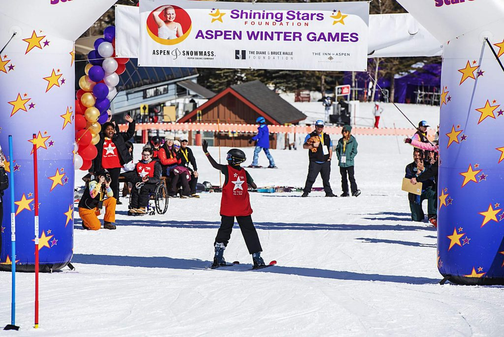 A child with the Shining Stars Foundation crosses the race finish line and waves as spectators cheer during the Aspen Winter Games at Buttermilk on Thursday, March 5, 2020.