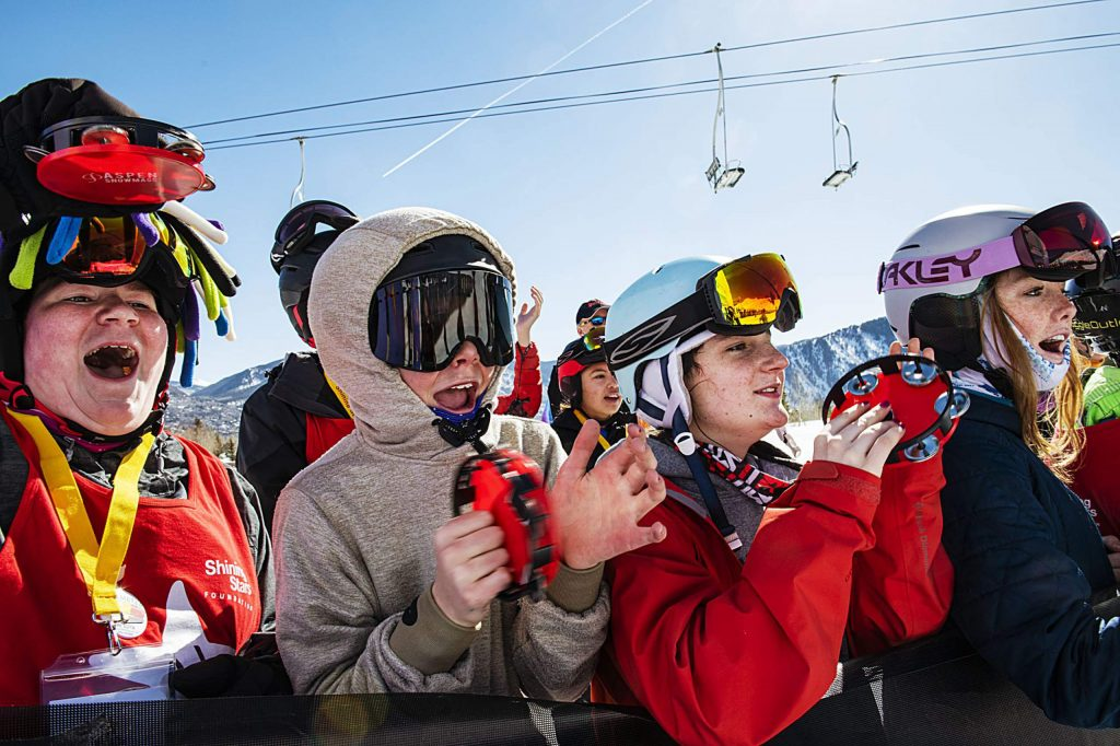 Shining Stars and volunteers cheer on racers from the side of the course during the Aspen Winter Games at Buttermilk on Thursday, March 5, 2020.