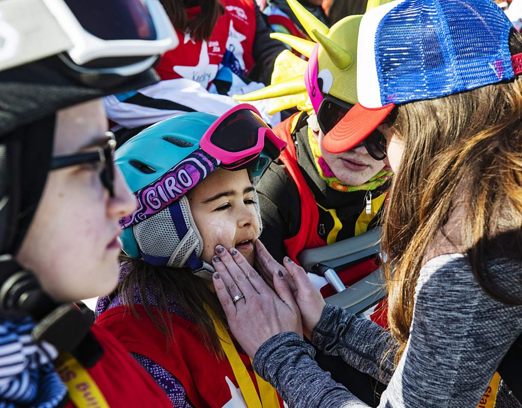 Shining Stars ski instructor Becca Crook puts sunscreen on Erika Grigoryan, 9, at the beginning of the Aspen Winter Games at Buttermilk on Thursday, March 5, 2020.