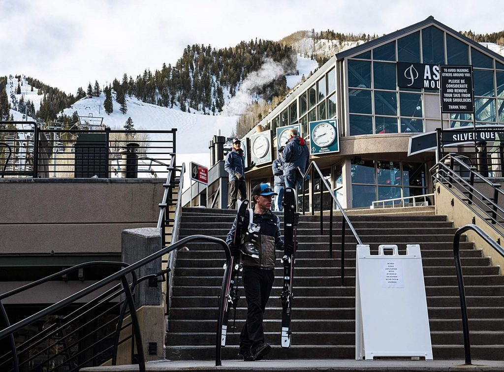 People remove skis from the base of Aspen Mountain on the first morning after the Governor ordered the closure of ski resorts on Sunday, March 15, 2020. (Kelsey Brunner/The Aspen Times)