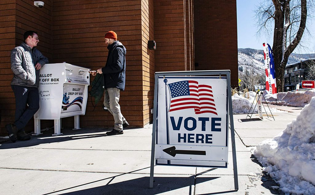 Jeff McMahan, left, leans against the ballot drop off box outside of the Pitkin County government building while his friend Nick Calderone votes for the presidential primaries on Super Tuesday on Tuesday, March 3, 2020. (Kelsey Brunner/The Aspen Times)